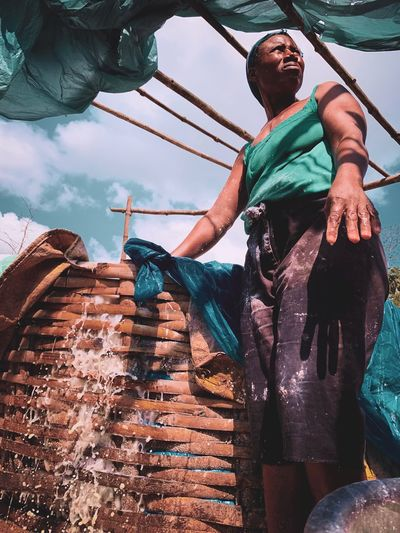Low angle view of man looking away while standing by basket against sky