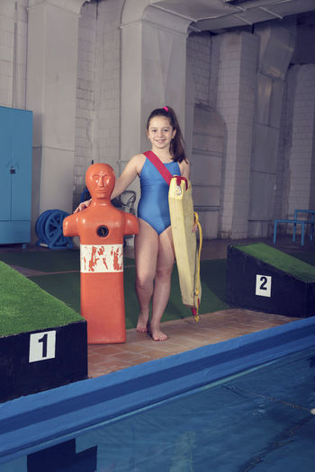 Portrait of girl with cpr dummy standing at swimming pool