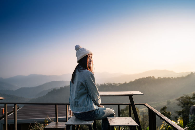 Woman sitting on stool in balcony against mountain during winter