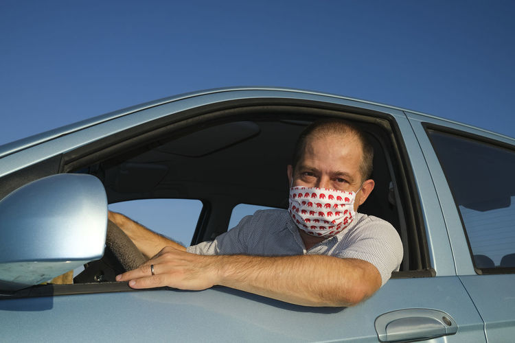 Man wearing a homemade face mask in a car as a covid19 prevention