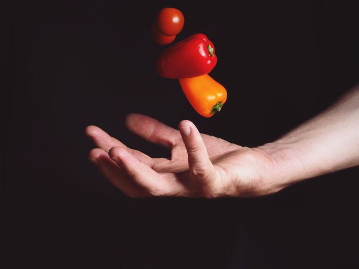 Close-up of hand holding tomato over black background
