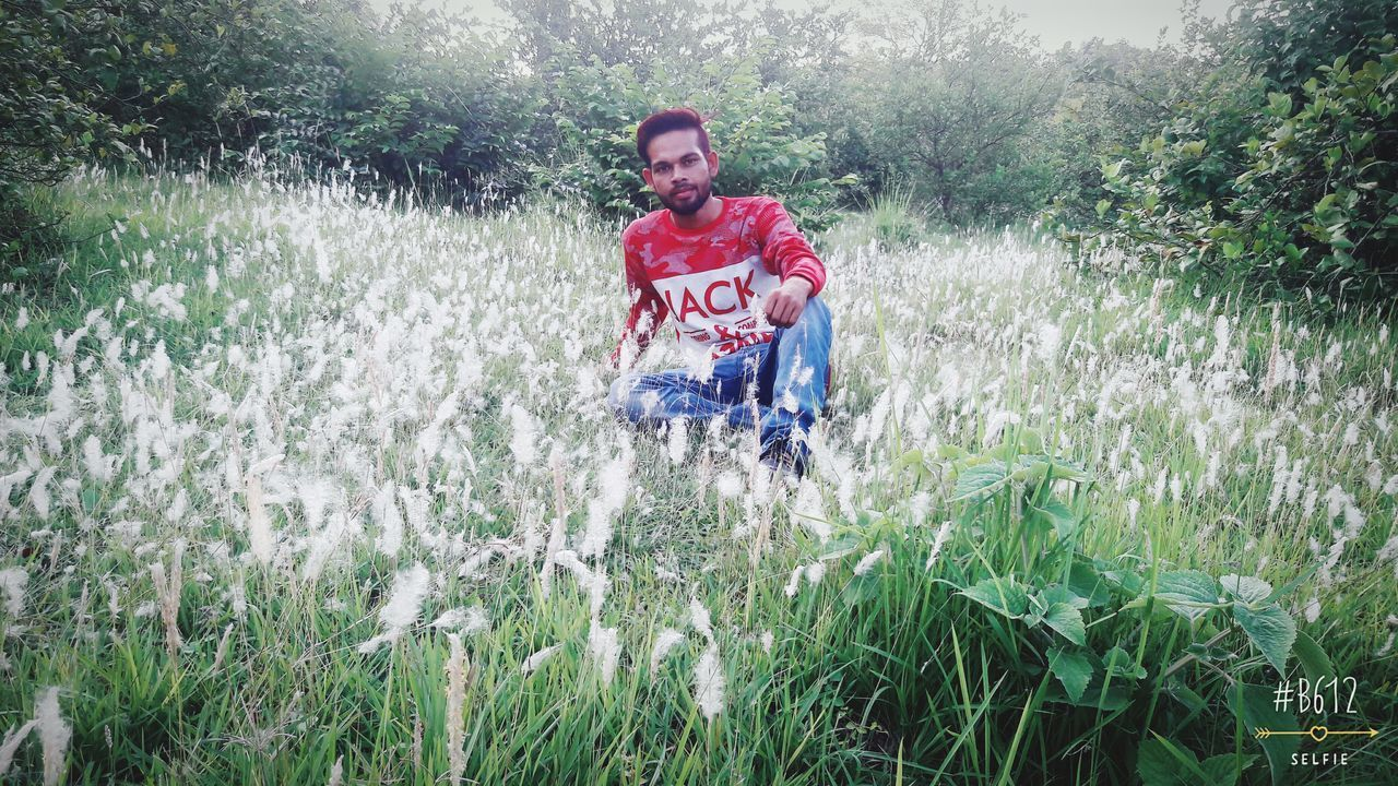 grass, looking at camera, front view, one person, nature, casual clothing, day, outdoors, portrait, full length, field, leisure activity, growth, smiling, happiness, rural scene, freshness, one man only, real people, adventure, young adult, adult, tree, adults only, only men, people