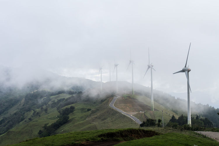 Agriculture Beauty In Nature Clean Energy Cloud - Sky Day Fog Landscape Mountain Mountain Range Nature No People Outdoors Rural Scene Scenics Sky Tranquil Scene Windmill Windpower