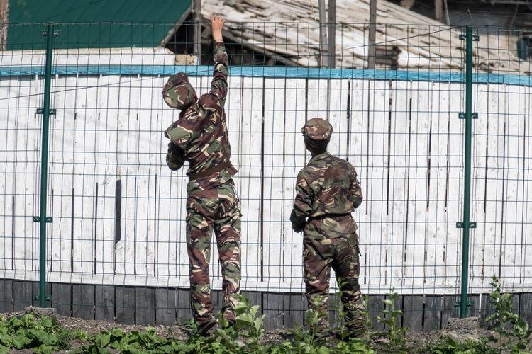 Full length of man standing against fence