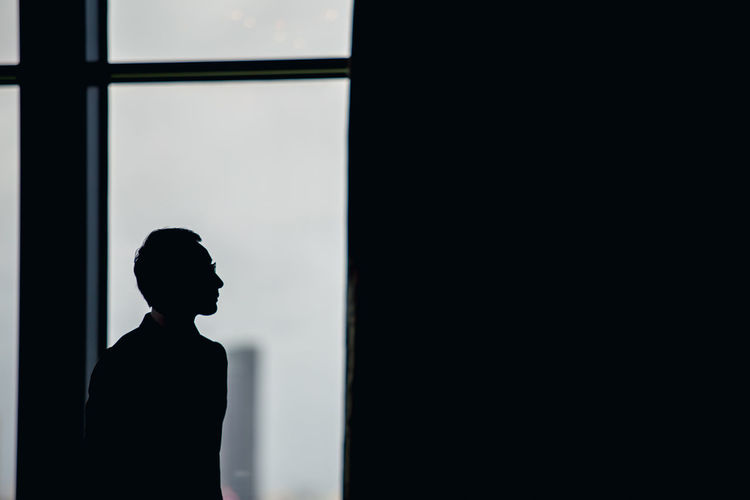 Side view of silhouette man standing against window