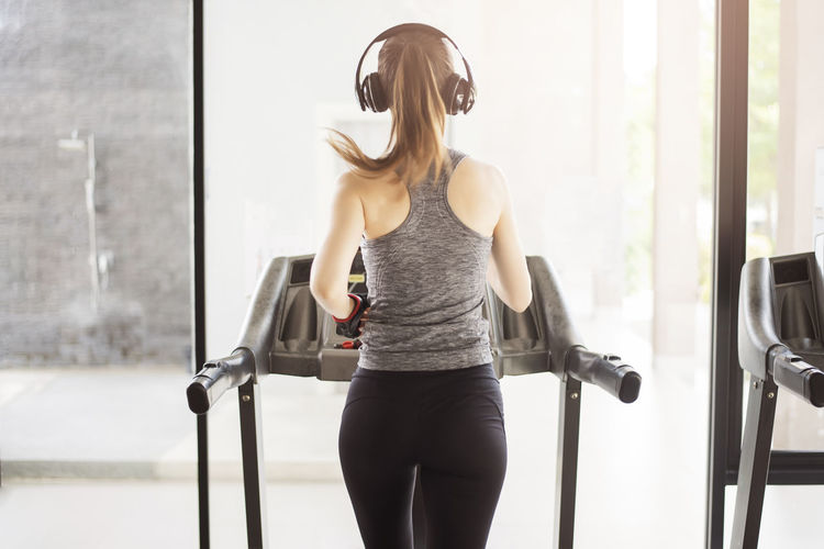 Rear view of woman listening music while running on treadmill at gym