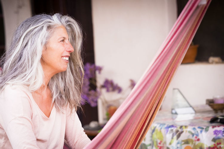 Smiling woman looking away while sitting at home