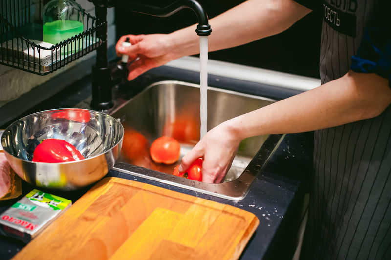 Midsection of woman cleaning vegetables in kitchen sink