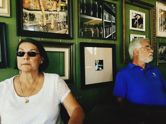 Senior Man And Woman Looking Away While Sitting Against Picture Frames On Wall
