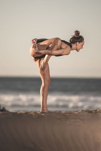 Side view of cheerful muscular woman doing yoga asana on one leg standing on sandy beach Sea Sky One Person Lifestyles Beach Land Water Horizon Horizon Over Water Full Length Balance Real People Healthy Lifestyle Standing Leisure Activity Nature Beauty In Nature Hairstyle Yoga Woman Standing Sunlight Asana Environment Copy Space