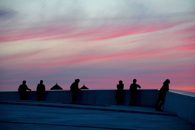 People on building terrace against sky during sunset