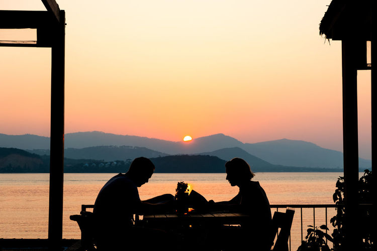 Silhouette people sitting at table by sea against clear sky during sunset