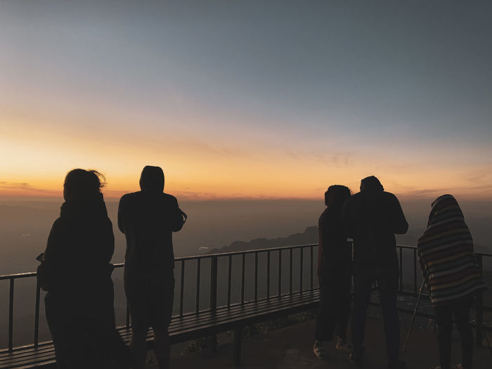 People standing at observation point against sky during sunset