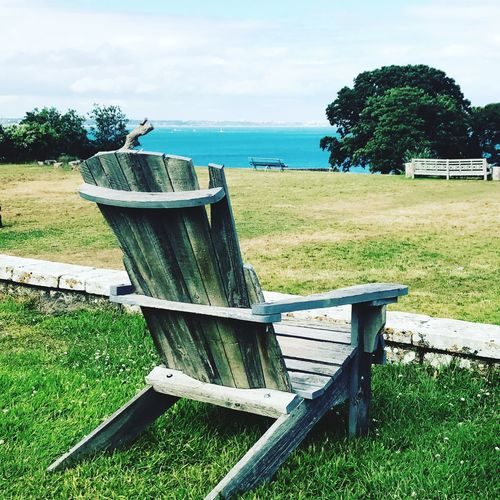 Plant Water Land Sky Grass Nature Day Seat Sea No People Tree Tranquility Beach Chair Beauty In Nature Cloud - Sky Tranquil Scene Green Color Scenics - Nature Outdoors