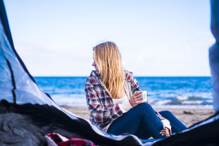 Woman sitting with coffee cup at beach against sky seen from tent