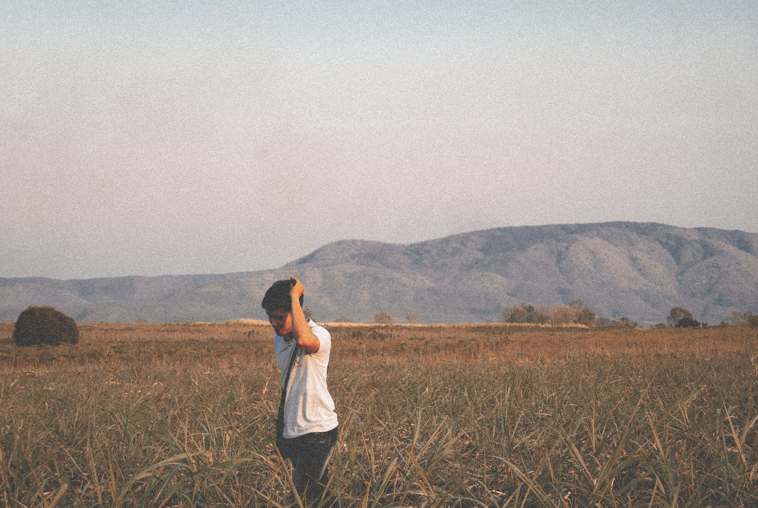one person, field, land, landscape, standing, sky, environment, mountain, nature, scenics - nature, casual clothing, beauty in nature, leisure activity, young adult, non-urban scene, tranquility, day, real people, plant, outdoors, hairstyle