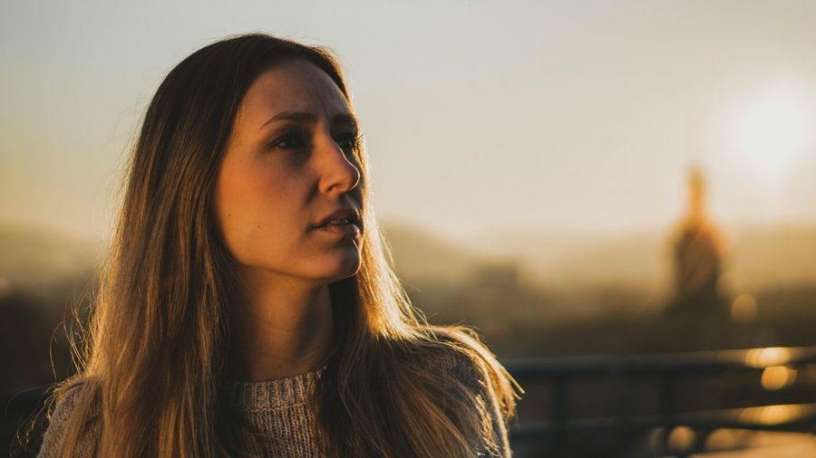 Thoughtful young woman looking away against sky during sunset