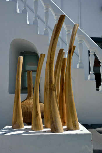 artistic wooden designed object displayed in the street of Mykonos No People Hanging Still Life Wood - Material In A Row Wall - Building Feature White Color Table Close-up Day Architecture Side By Side Nature Built Structure Sunlight Textile Art Art And Craft ArtWork Design Outdoors Installation Art Mykonos,Greece