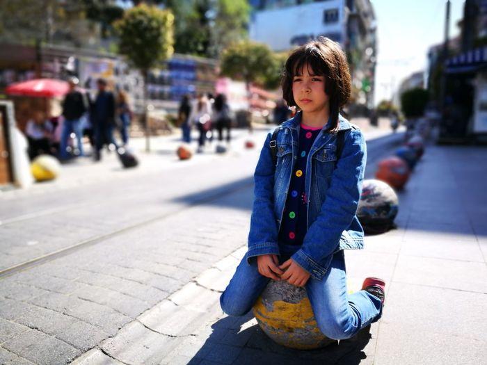 Girl kneeling on sidewalk in city