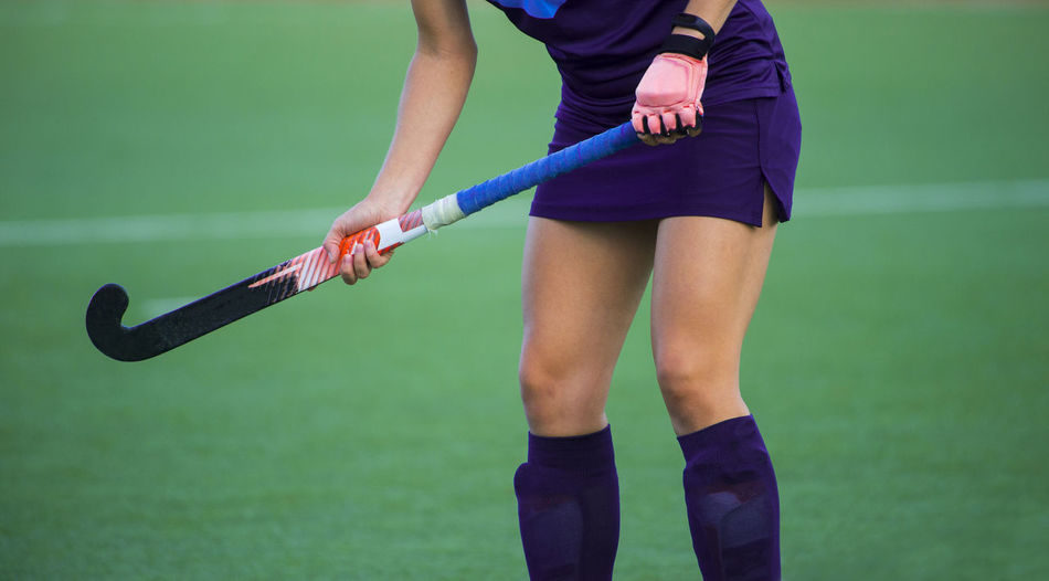 Young hockey player woman with ball in attack playing field hockey game Field Field Hockey Review Field Hockey Fight Grass Green Color Active Ball Body Part Casual Clothing Day Focus On Foreground Green Color Holding Human Body Part Human Leg Leisure Activity Lifestyles Low Section Midsection One Person Playing Playing Field Real People Shorts Sport Sports Sports Clothing Standing Stick Team
