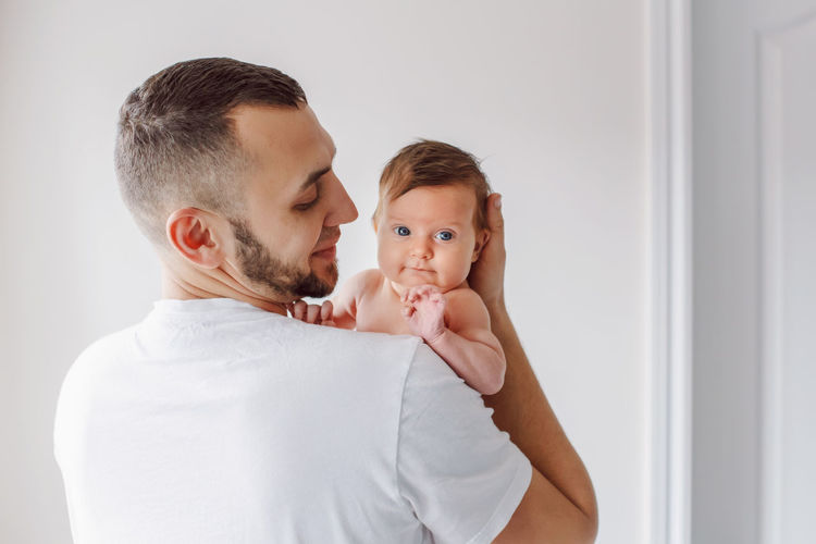 Man holding baby girl at home