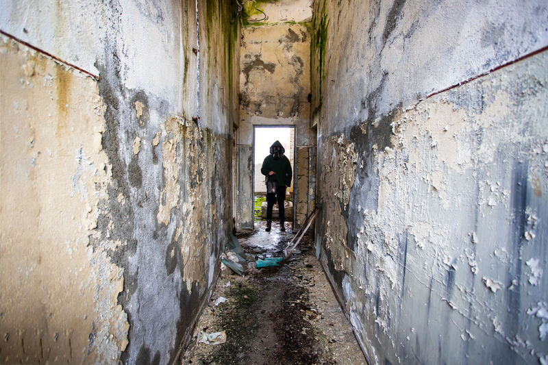 Rear view of man standing in old building