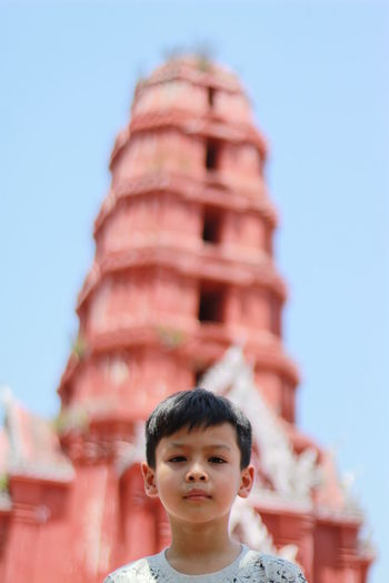 Portrait of boy at temple against clear sky