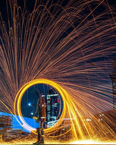 Light trails on illuminated ferris wheel at night