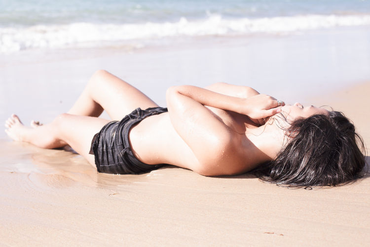 Sensuous Young Woman Lying On Shore