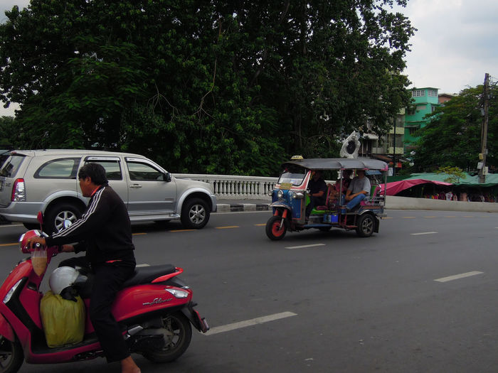 Side view of man motor scooter on roadside