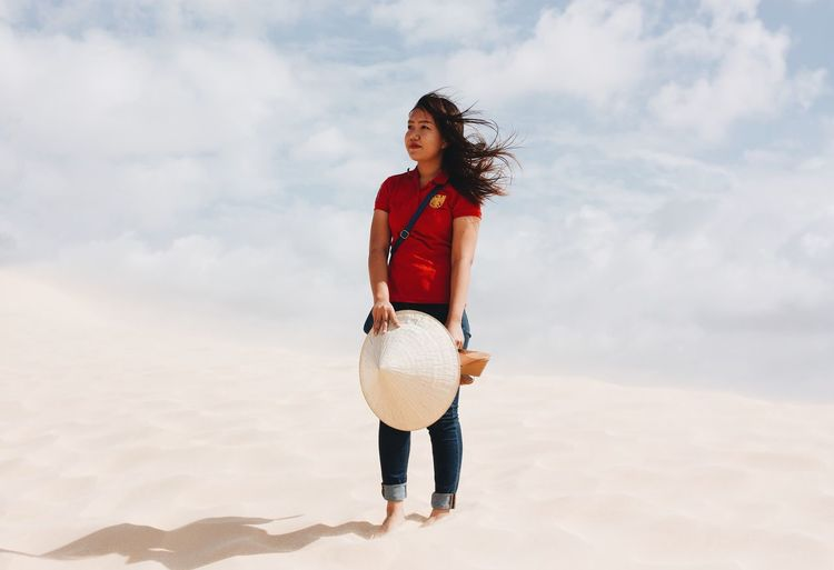 Woman holding asian style conical hat while standing in desert against sky during sunny day