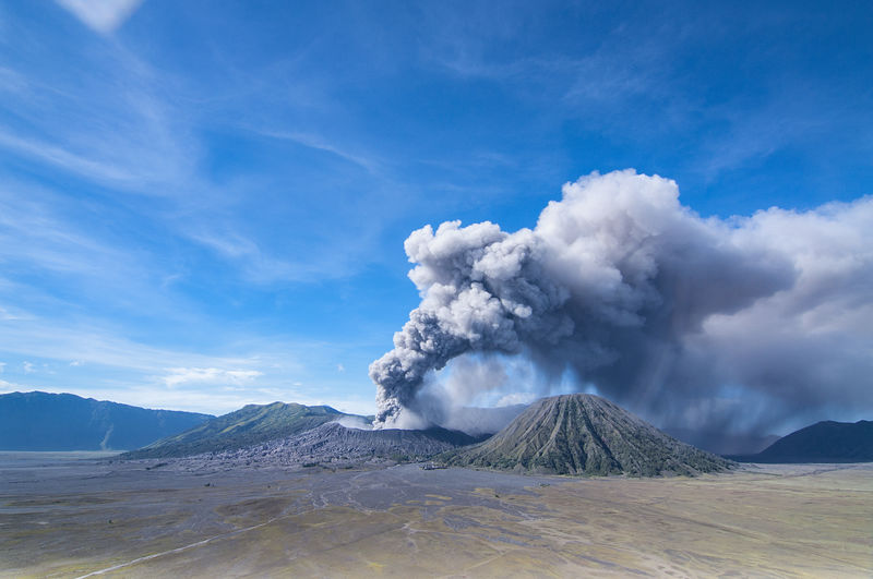 Scenic view of an active volcano against cloudy sky