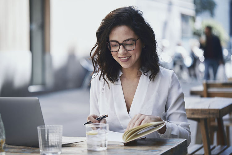 Smiling businesswoman writing in diary while sitting at sidewalk cafe