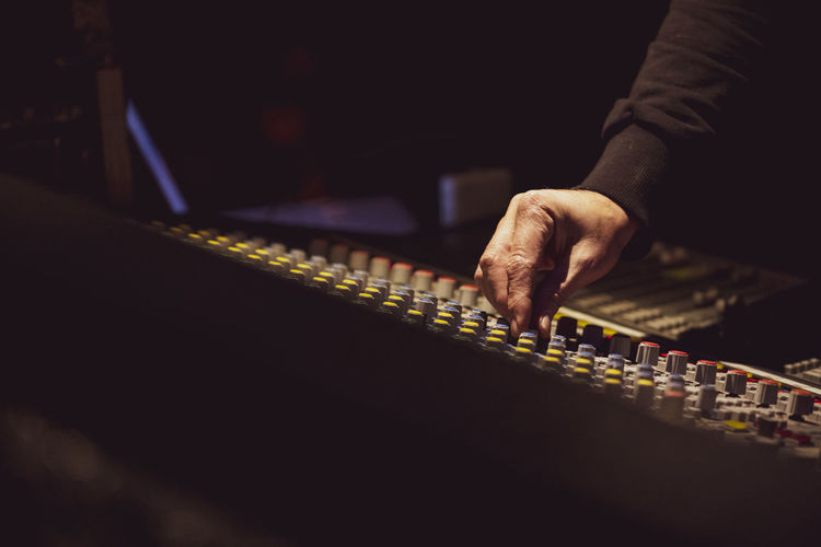 Cropped hand of musician adjusting sound mixer in nightclub