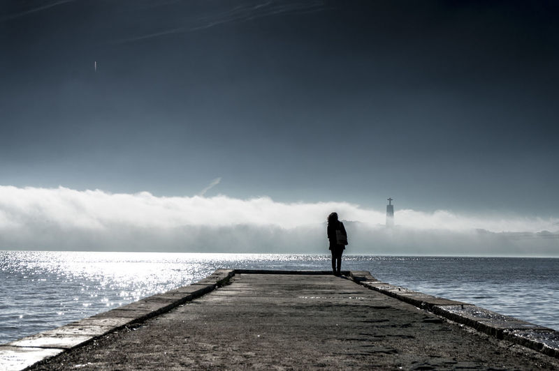 Silhouette woman standing on jetty at sea against sky during sunny day