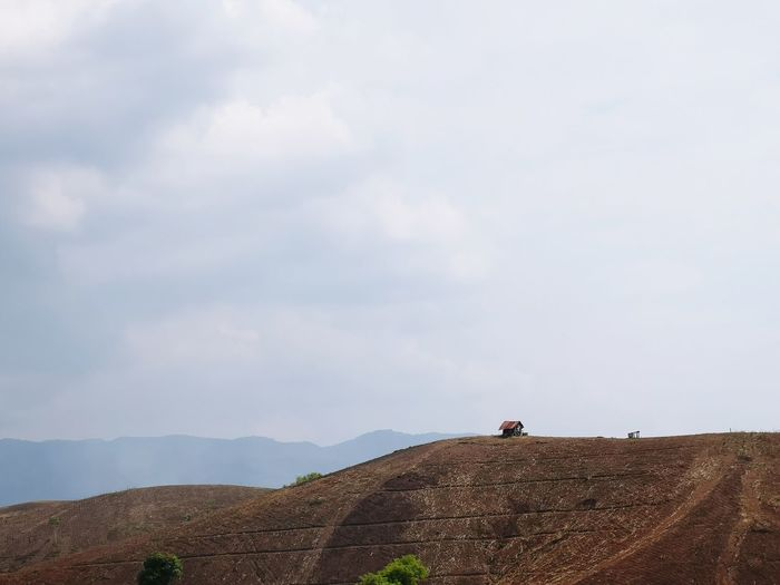 People riding motorcycle on land against sky