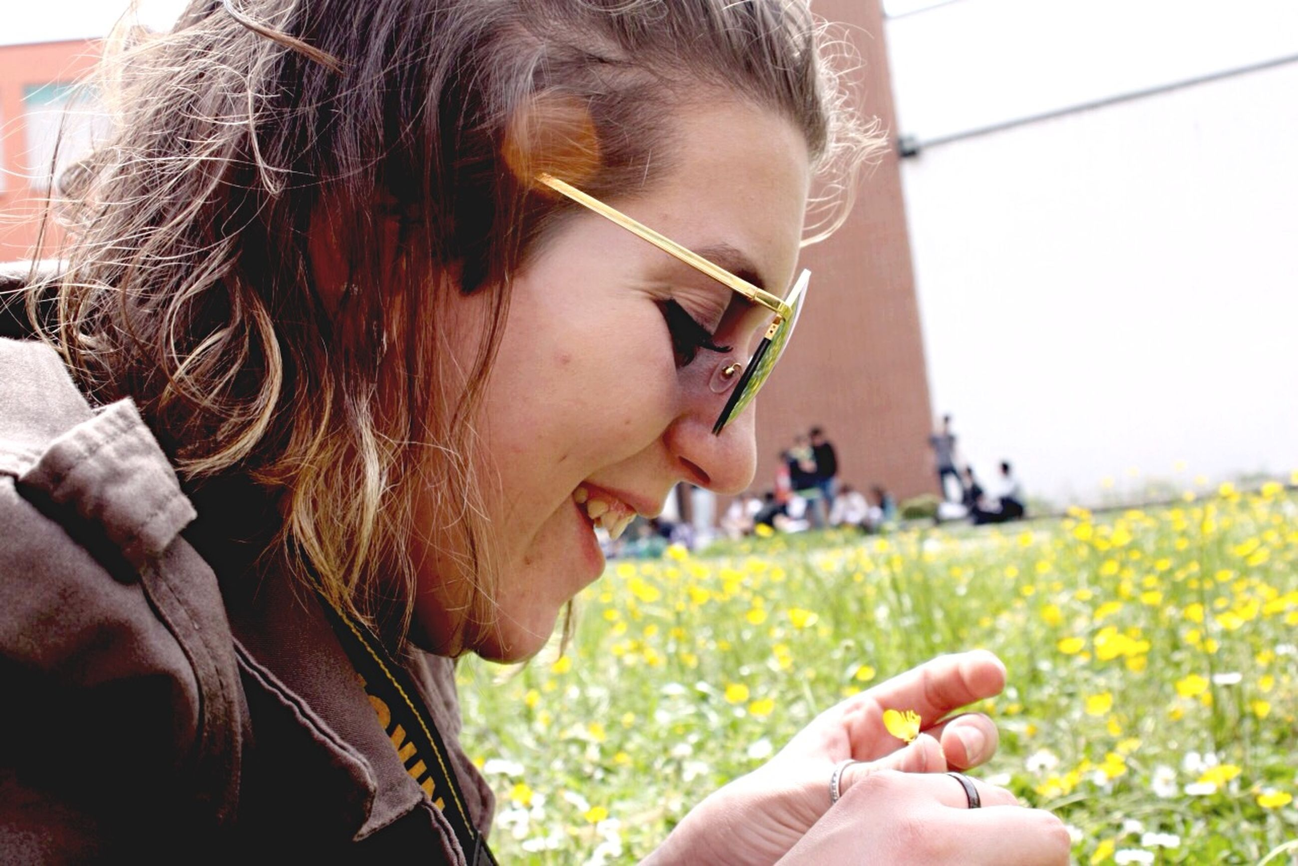 person, holding, lifestyles, focus on foreground, field, part of, leisure activity, close-up, flower, grass, cropped, headshot, day, sunlight, outdoors