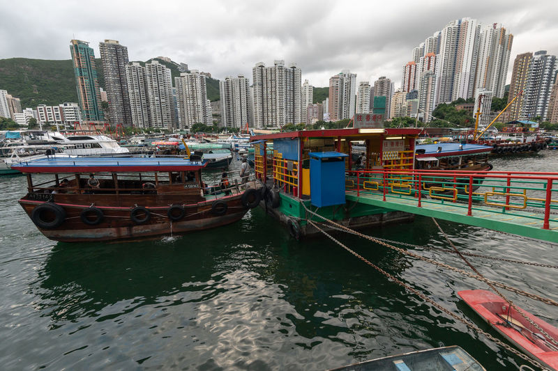 Boats moored in city by buildings against sky
