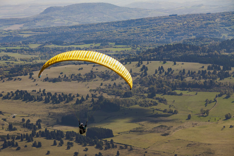 Person Paragliding Over Landscape
