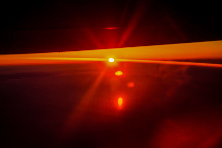 Close-up of illuminated red lights against sky at sunset