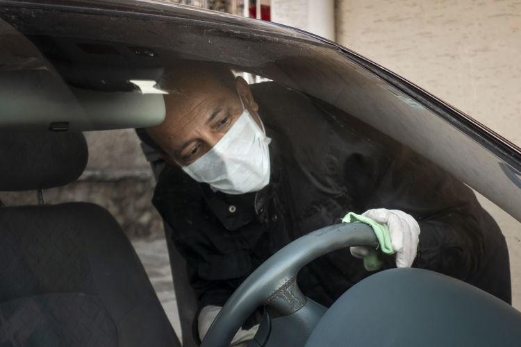 Man wearing mask cleaning steering wheel in car