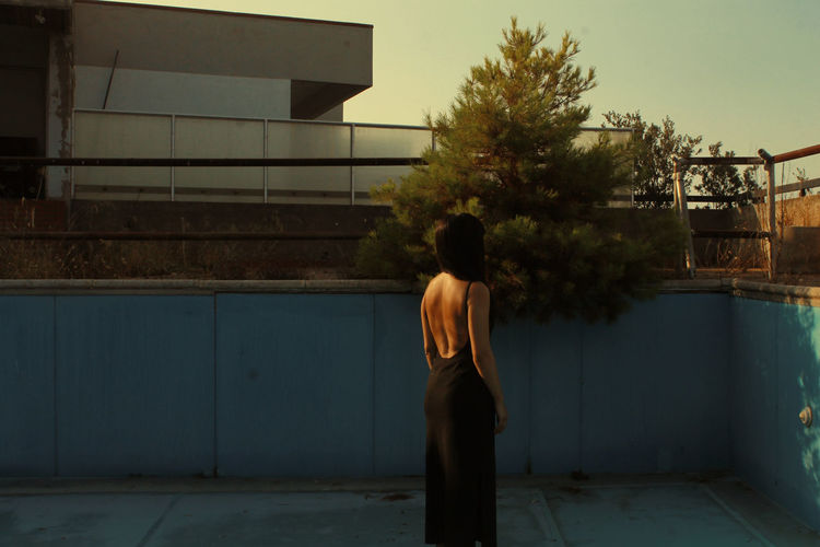 Rear view of woman standing by swimming pool against building