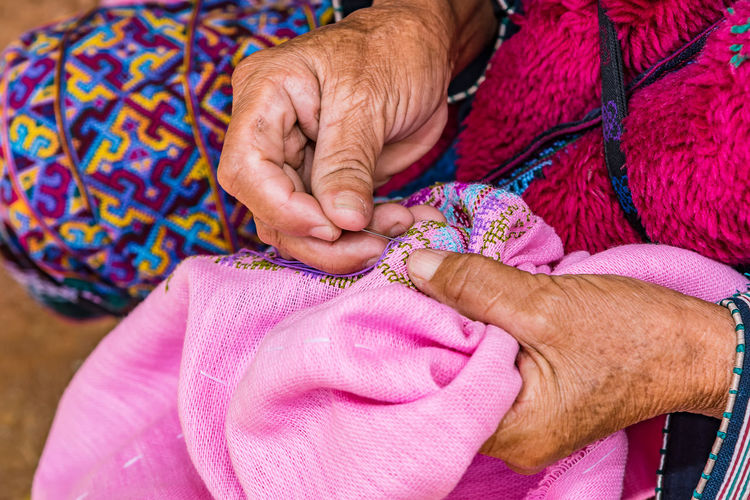 Midsection of woman sewing pink textile