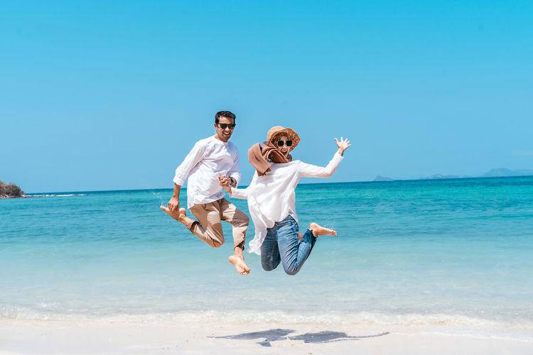 Full length of men jumping over sea against sky