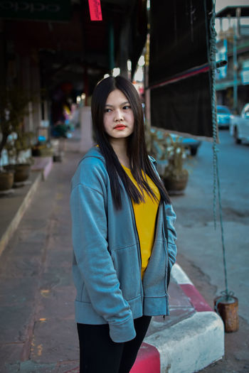 Portrait of young woman standing on street in city