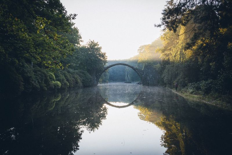 ARCHED REMOTE BRIDGE WITH WATER REFLECTION