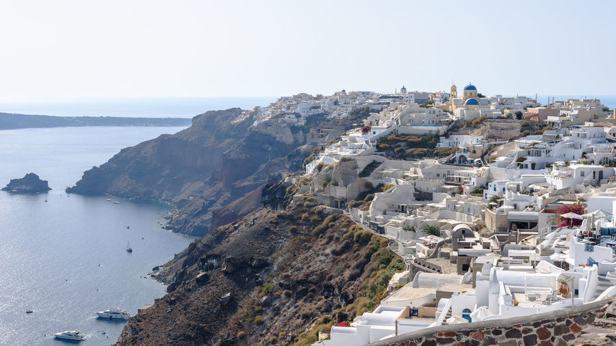 Finikia with Oia in the background on Santorini, Greece Finikia Architecture Beauty In Nature Building Exterior Built Structure Cityscape Clear Sky Cyclades Day High Angle View Hillside Horizon Over Water Nature No People Outdoors Scenics Sea Sky Tranquility Water
