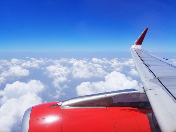 Cropped image of aircraft wing flying against blue sky