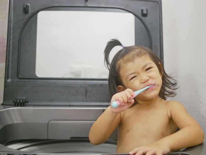 Portrait of shirtless girl brushing teeth in washing machine at home