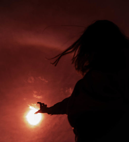 Silhouette woman gesturing while standing against orange sky